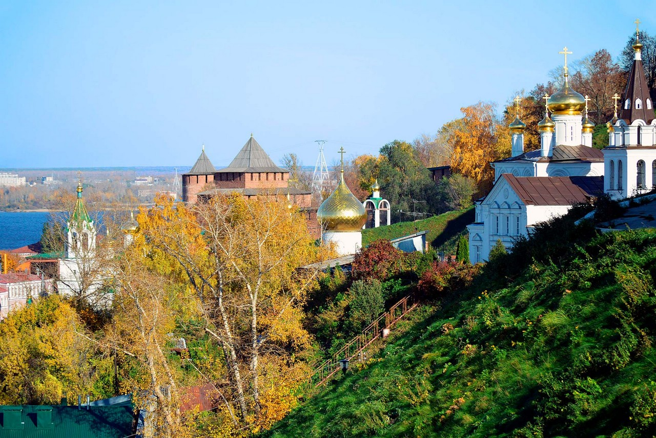 A church on the hill, towers and a river behind the trees
