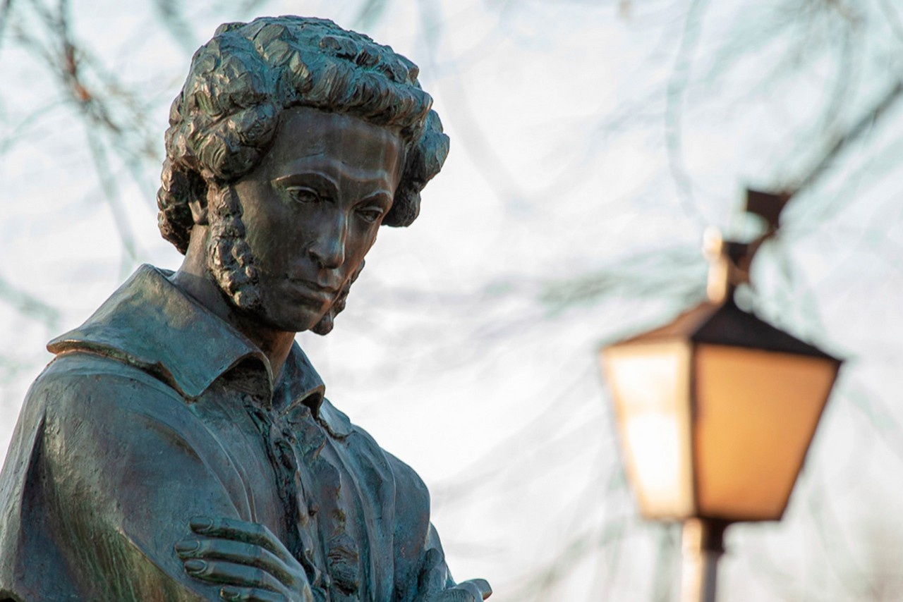 A face of a bronze monument of a famous Russian poet Pushkin, man with curly hair, a tree and a street light behind the monument
