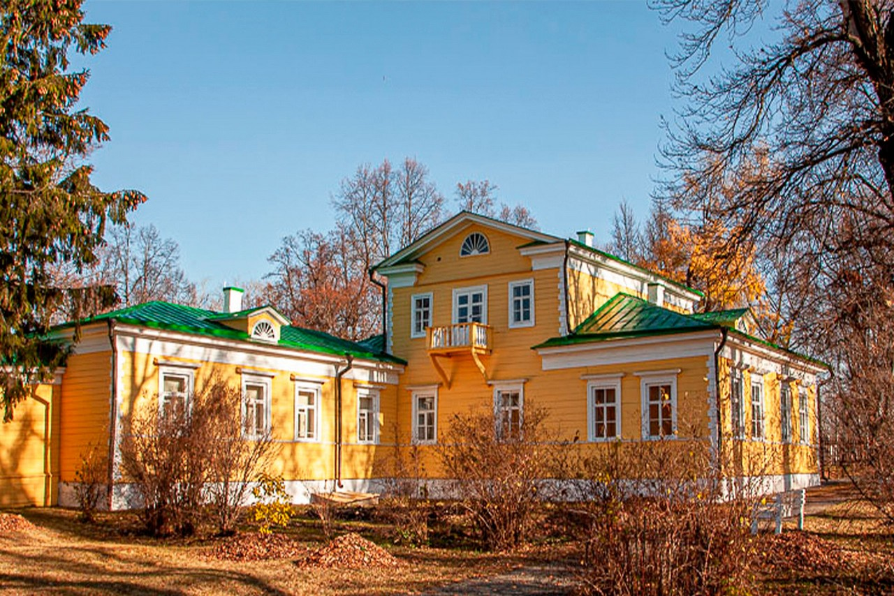 A wooden yellow building, mansion of a famous Russian poet Pushkin surrounded with yellow trees in autumn