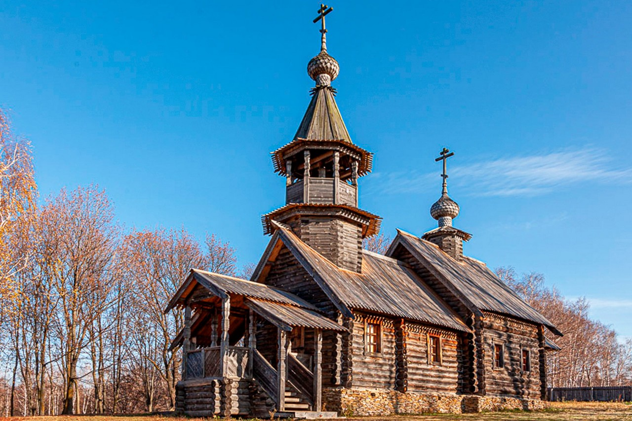 A small wooden church in a countryside with wooden bell-tower and domes in autumn