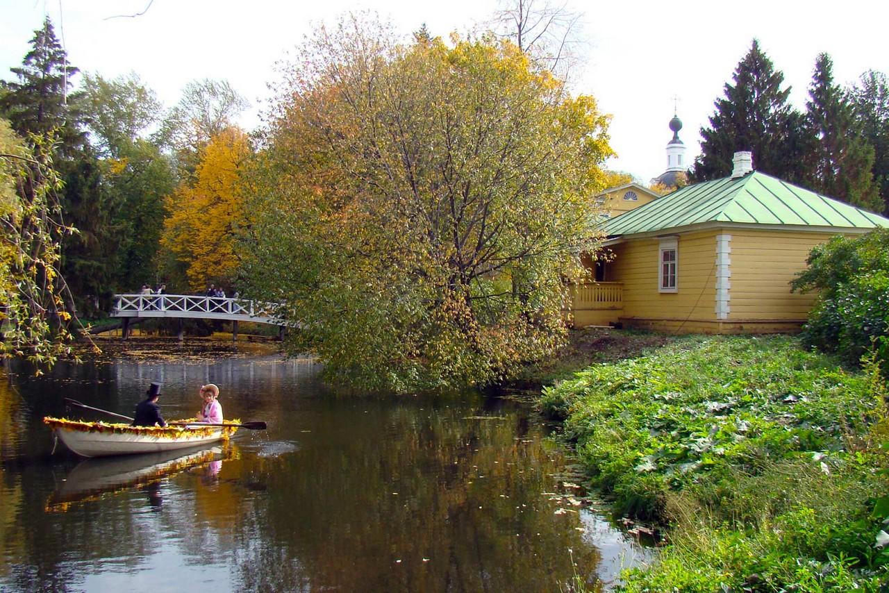 Autumn landscape in the countryside: two people wearing 19th century clothes on a small boat on a river, white wooden bridge and yellow wooden building behind them