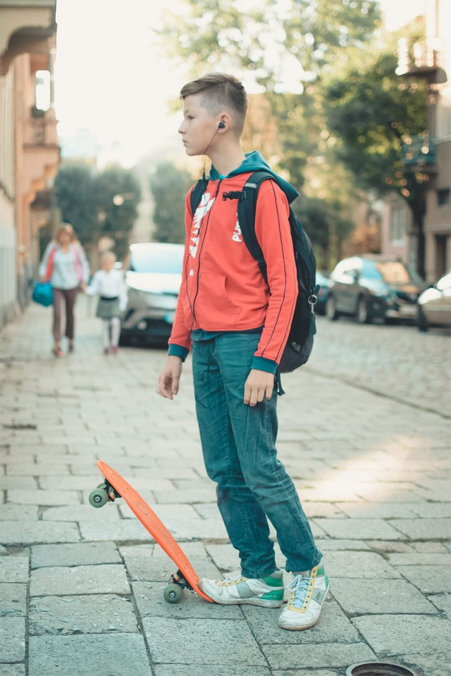 A boy with a backpack and earbuds with an orange skateboard in the middle of the street