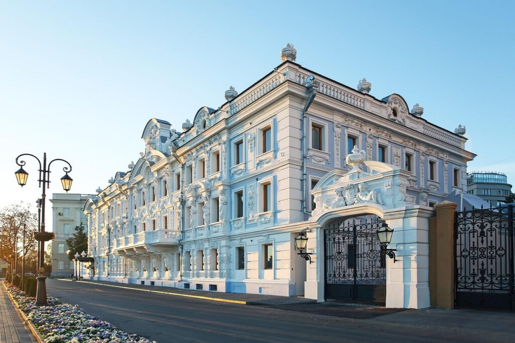 A 19-th century two-storey mansion with rich decoration built in eclectic style, gates with sculptures on the top