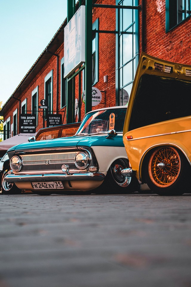 Retro cars in front of red brick building
