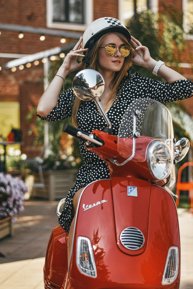 A young lady riding a red scooter Vespa