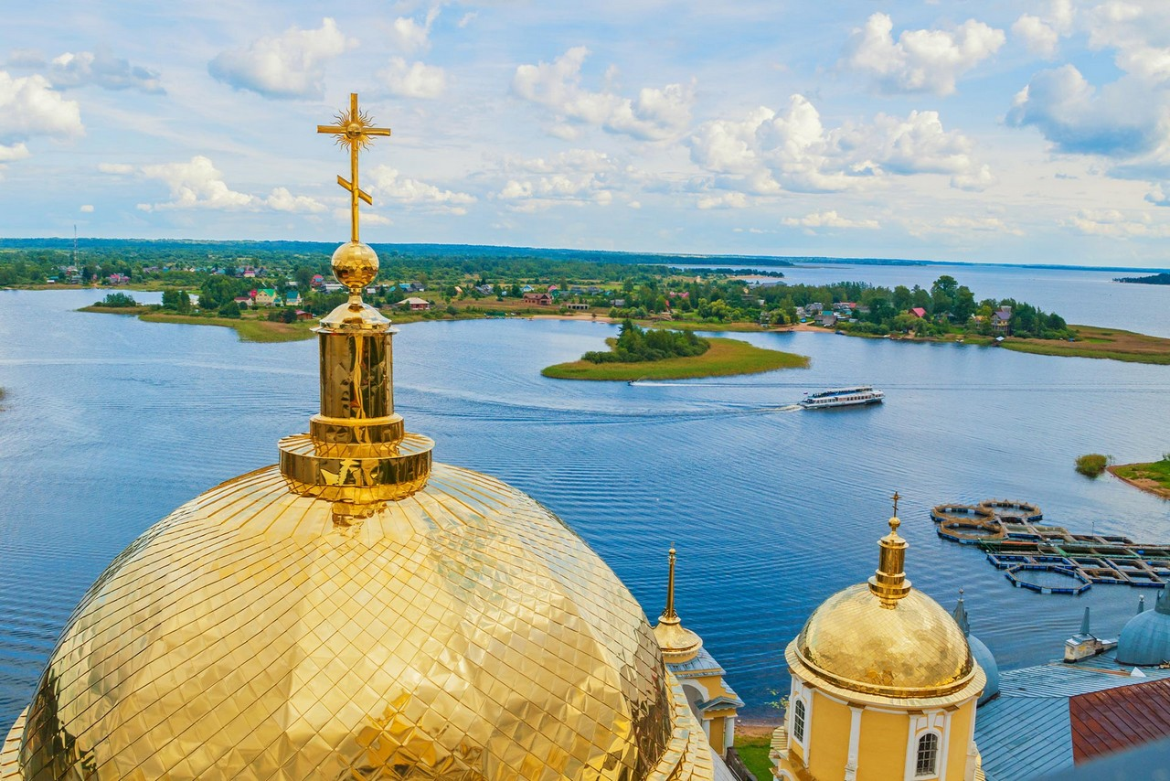 A view of one small and on big gilded dome of a cathedral with gilded cross on the top, view over a lake with some islands in the middle of it