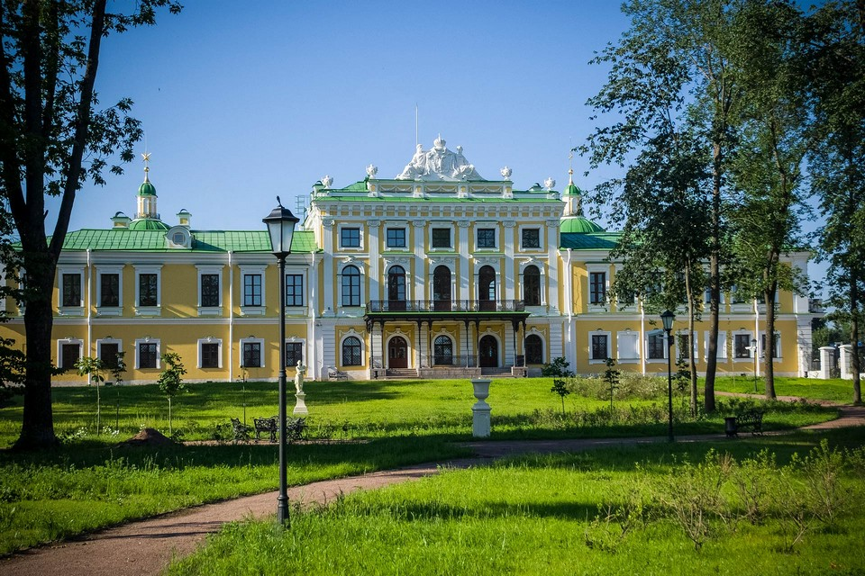 A yellow En Route Imperial Palace of Catherine the Great of the 18th century, built in the style of classicism with baroque elements, façade decorated with white columns and a sculpture on the top of the palace