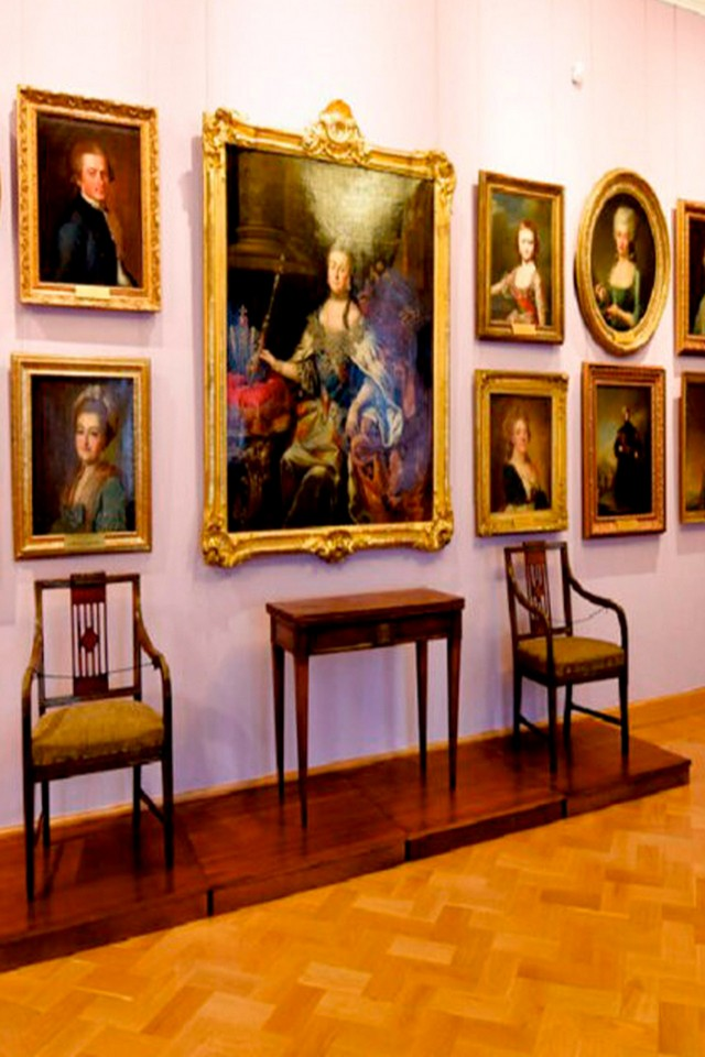 A wall in an Art Gallery with paintings, big portrait of the Empress Catherine the Great in the middle, historical table and two chairs
