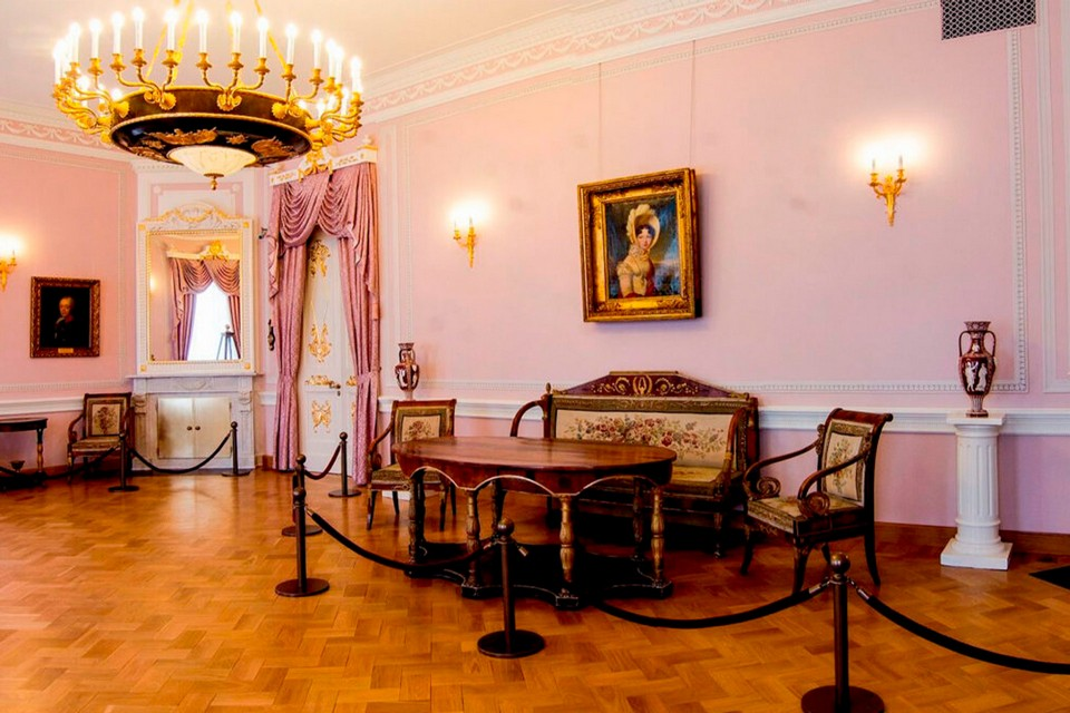 A hall in a royal palace with pink walls, massive chandelier, royal furniture and the 18th century paintings