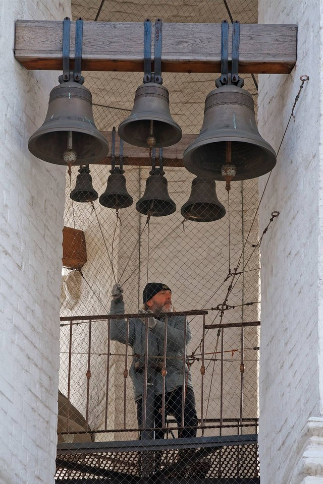 A man ringing the bells of a bell tower