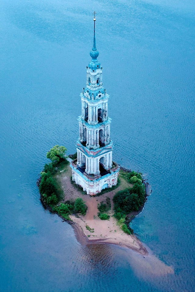 An old bell tower on a tiny desert island, neoclassical campanile rising to a height of 74.5 metres over the waters of the Uglich Reservoir on the Volga River