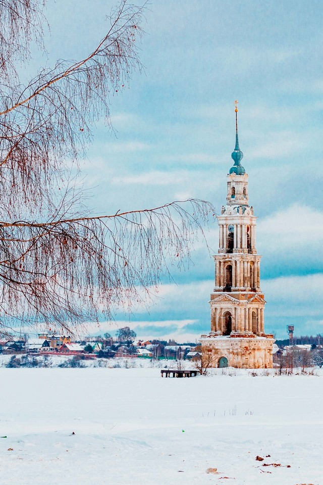 A view of an old bell tower on an island behind a tree in winter