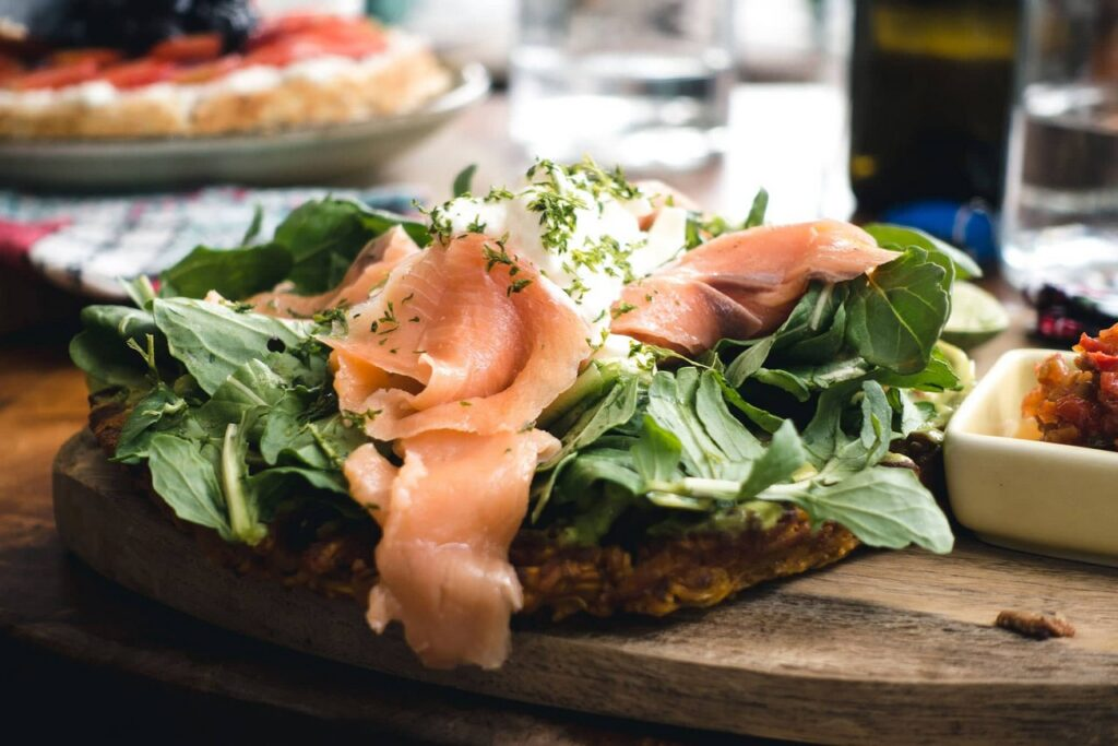 A sandwich with a lot of greens and salmon slices served in a restaurant