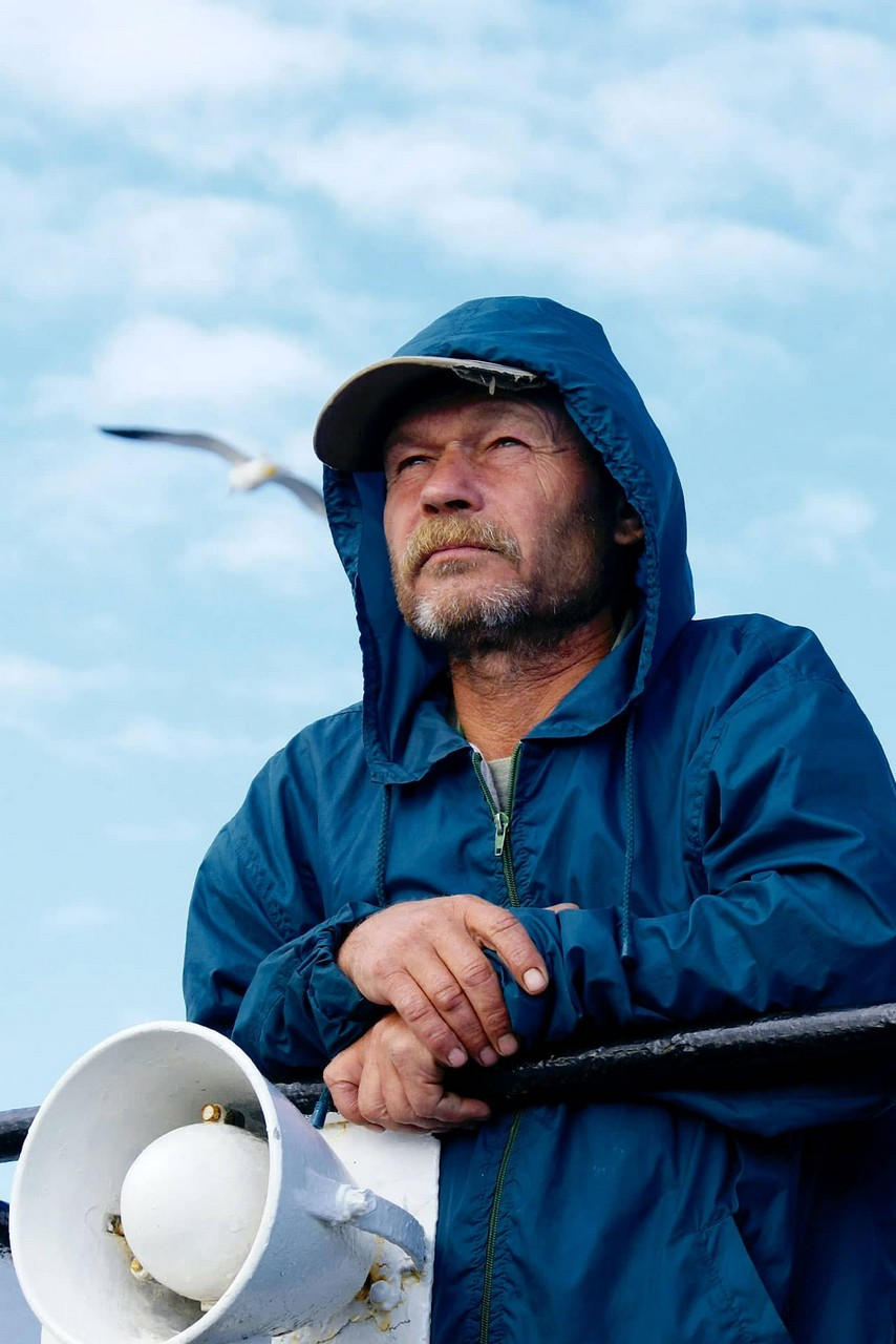 A man with a serious face watching the sea, man wearing a hooded windbreaker jacket with a loudspeaker in his hands, a seagull in the sky
