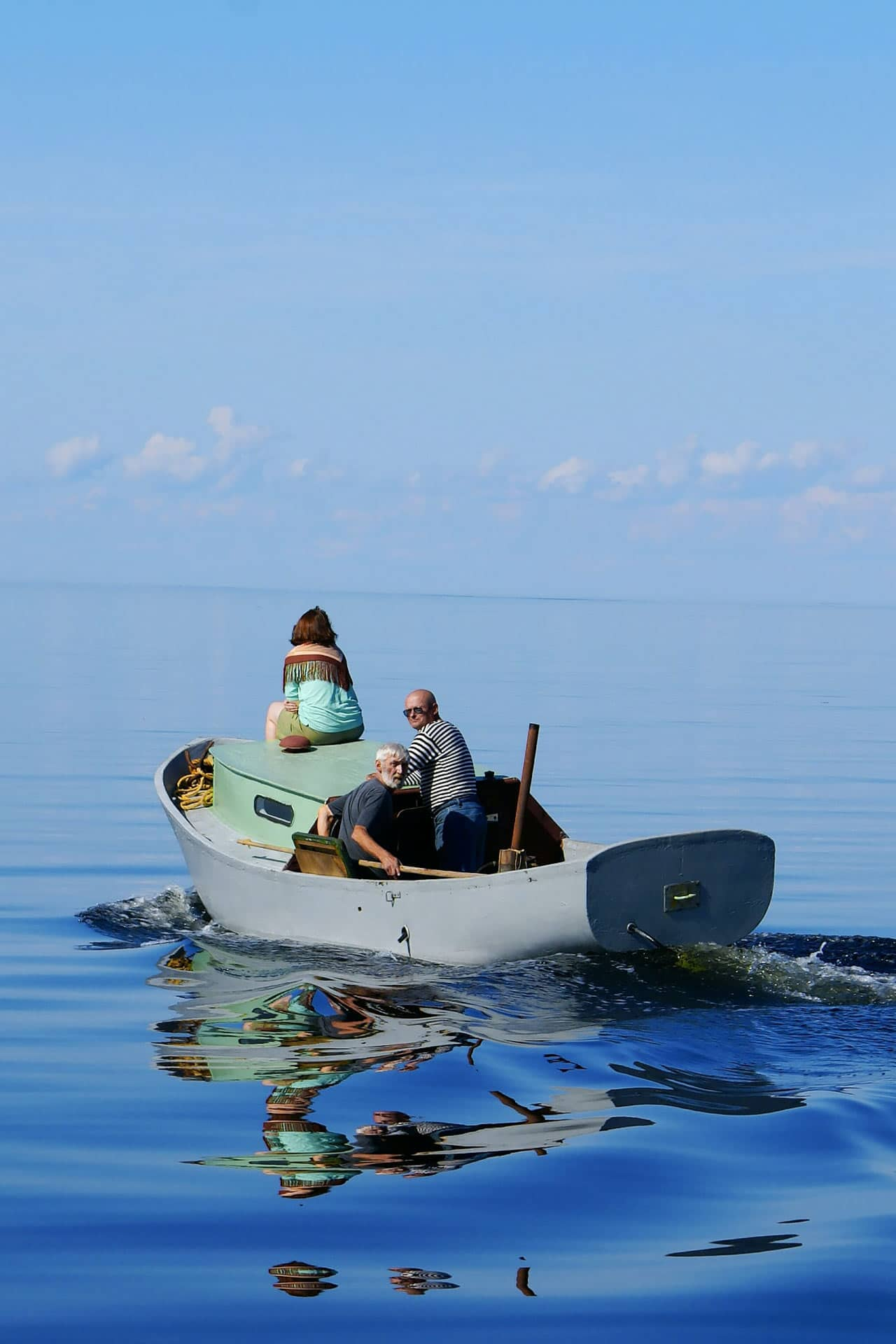 A fisher boat with three people in the sea, sky and sea of the same blue color