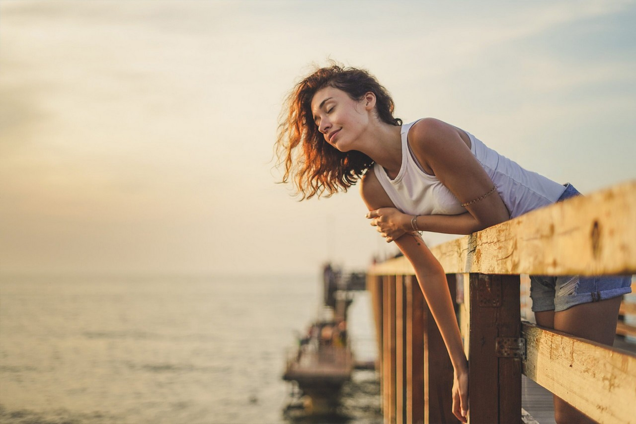 A young woman with curly hair chilling on the sea pier