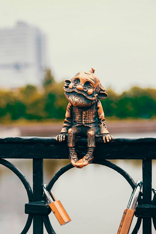A small bronze statue of an old man sitting on a bridge fence