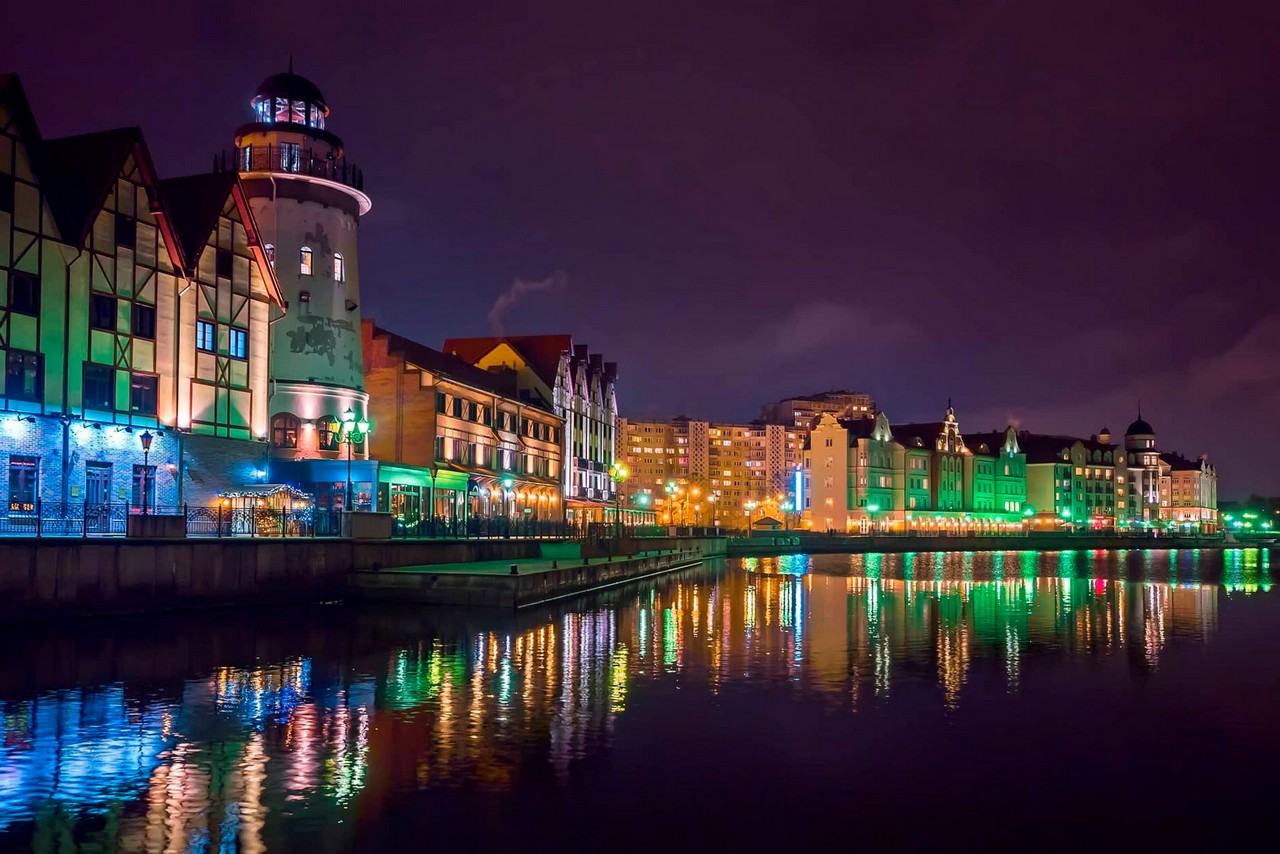 Illumined embankment of a river at night, buildings in German historical style on the embankment