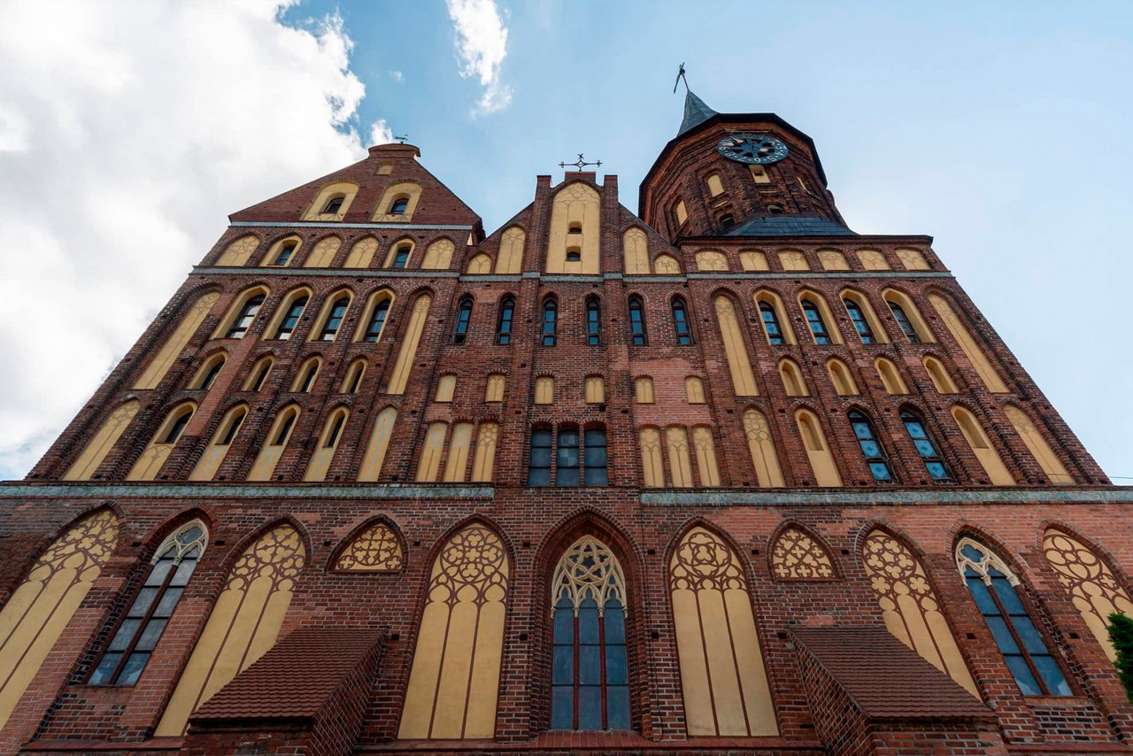 View from the ground of a gothic-style red brick cathedral with a clock tower