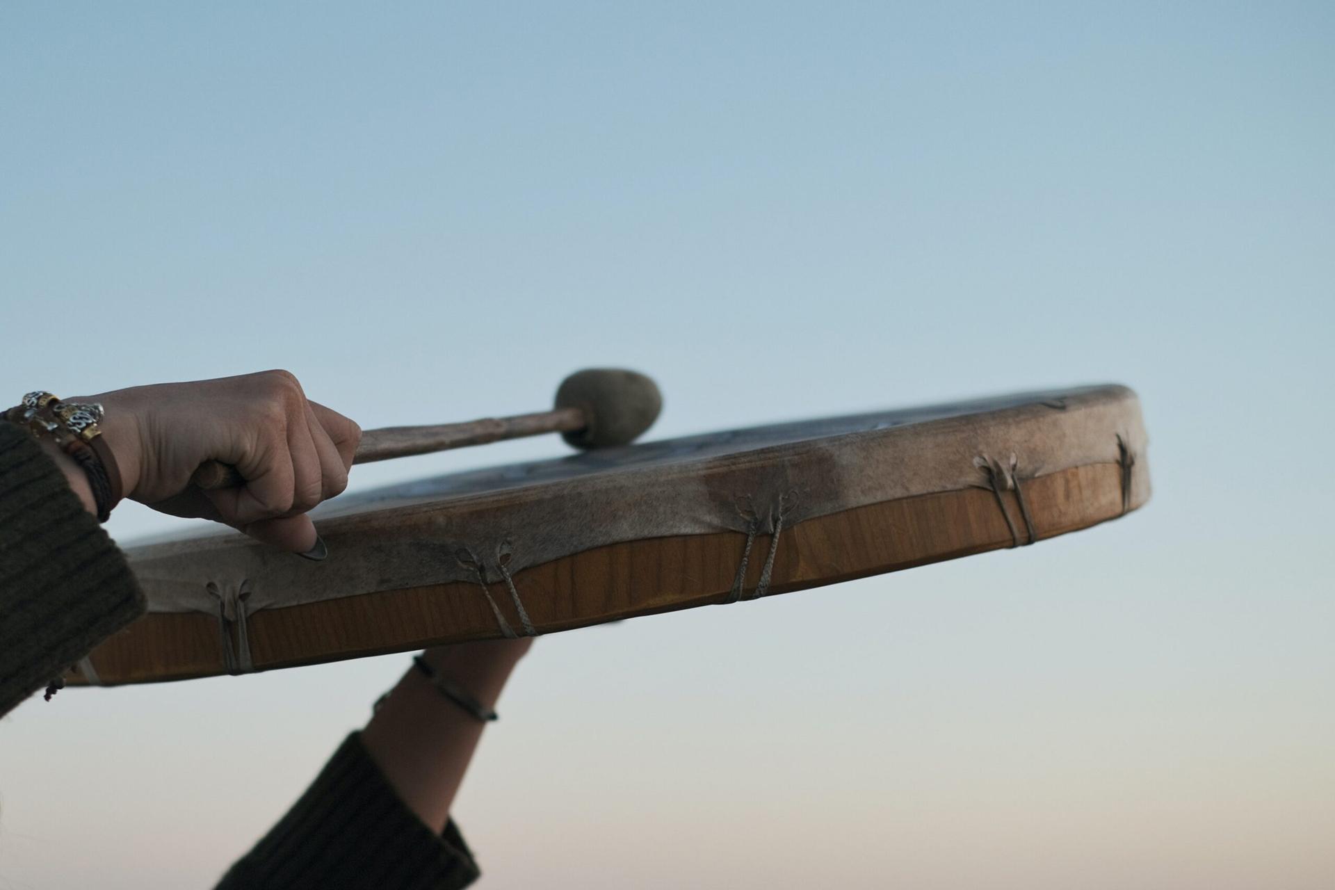 A man playing traditional shaman drum