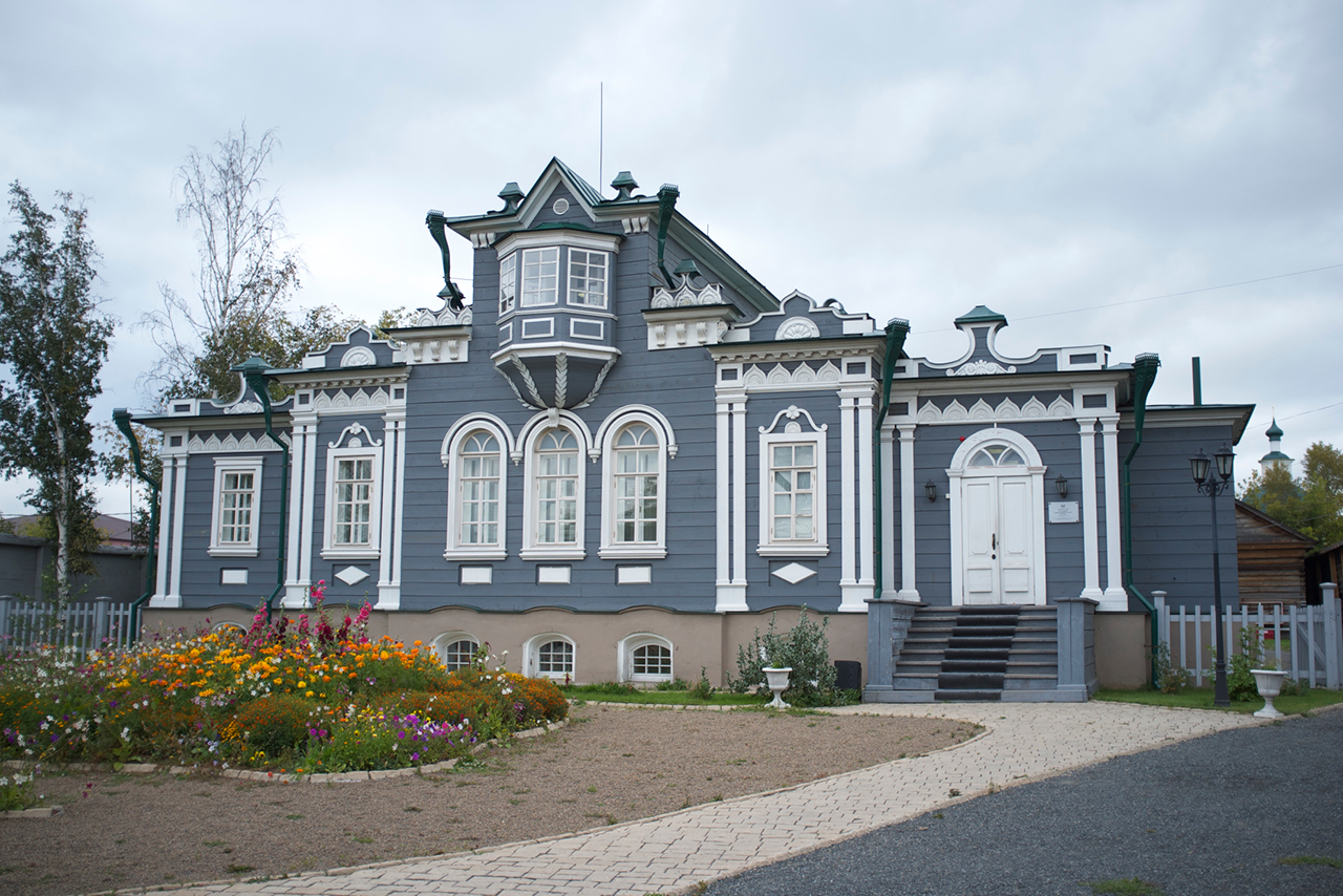 A grey and white wooden house built in the style of classical noble mansions decorated with a bay-window