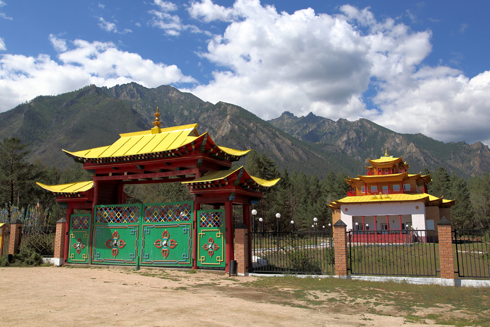 A Buddhist temple behind a fence with gates in oriental style in a beautiful place between mountains