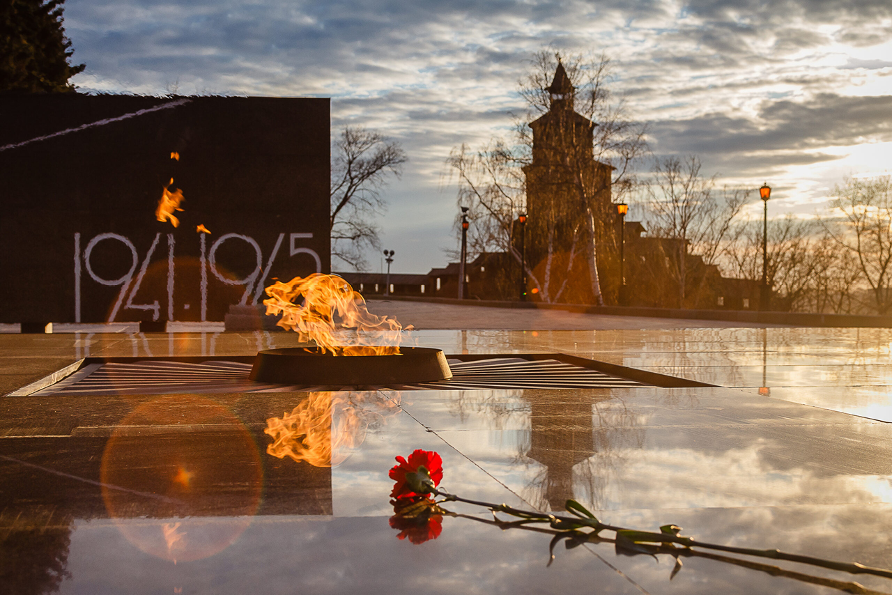 Eternal flame memorial, marble monument, a red clove flower, Kremlin tower in the background