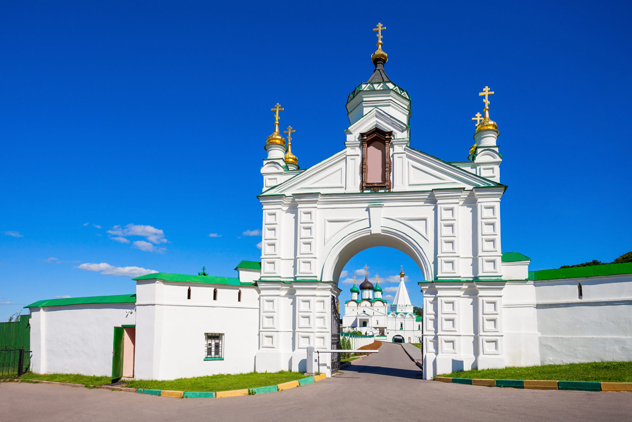 Main gates of a monastery, white wall and gates decorated with small gilded domes with crosses on the top, a cathedral on the distance