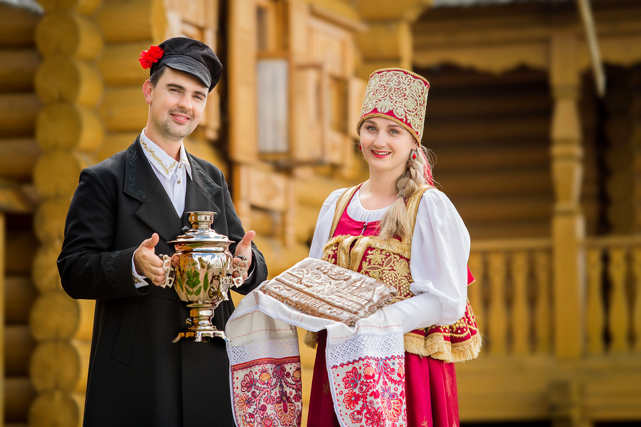 A couple wearing Russian traditional clothes hold a samovar and gingerbread in front of a wooden house