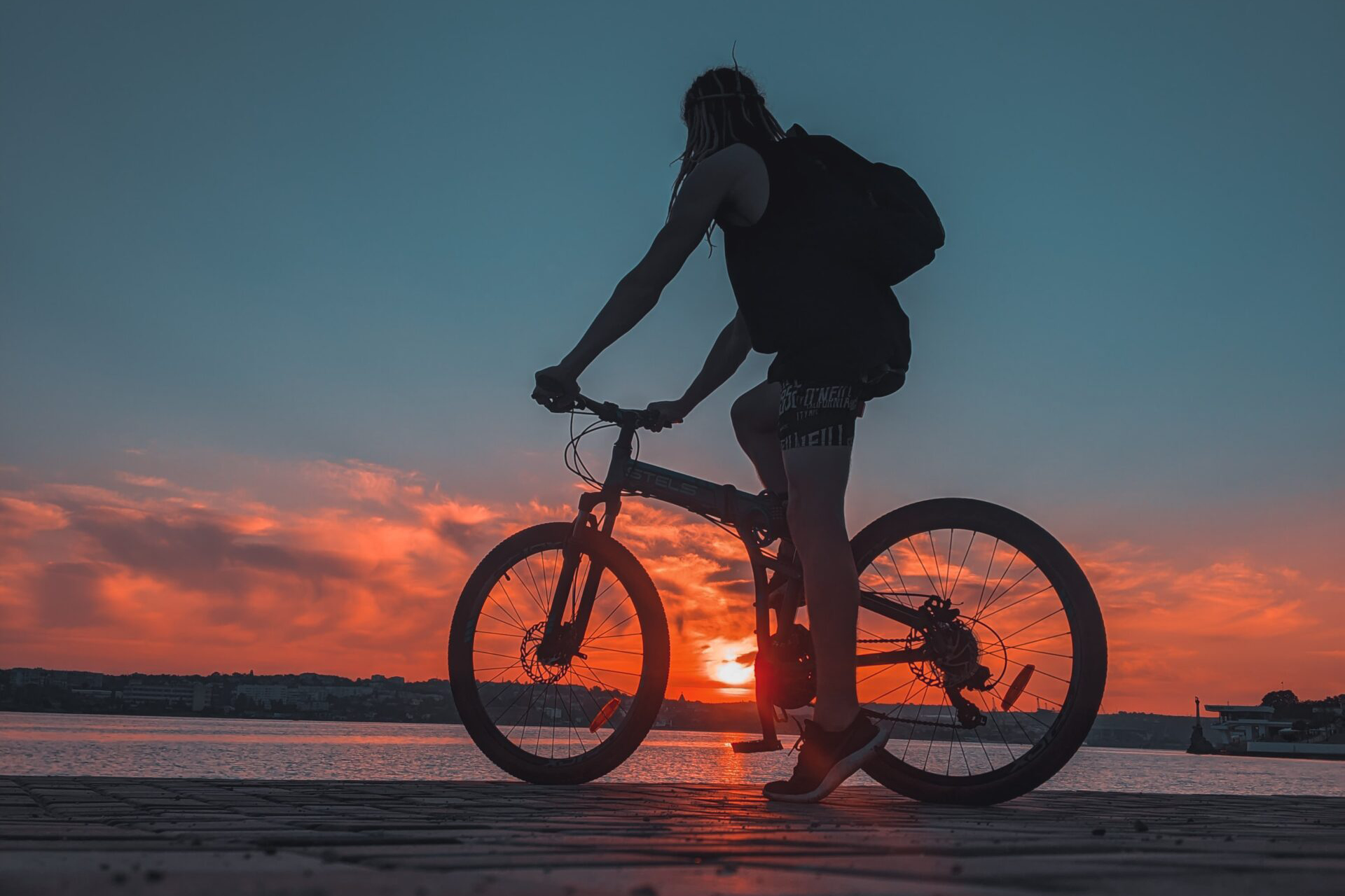 A biker in front of the sea during the sunset, city on the background, beautiful sunset