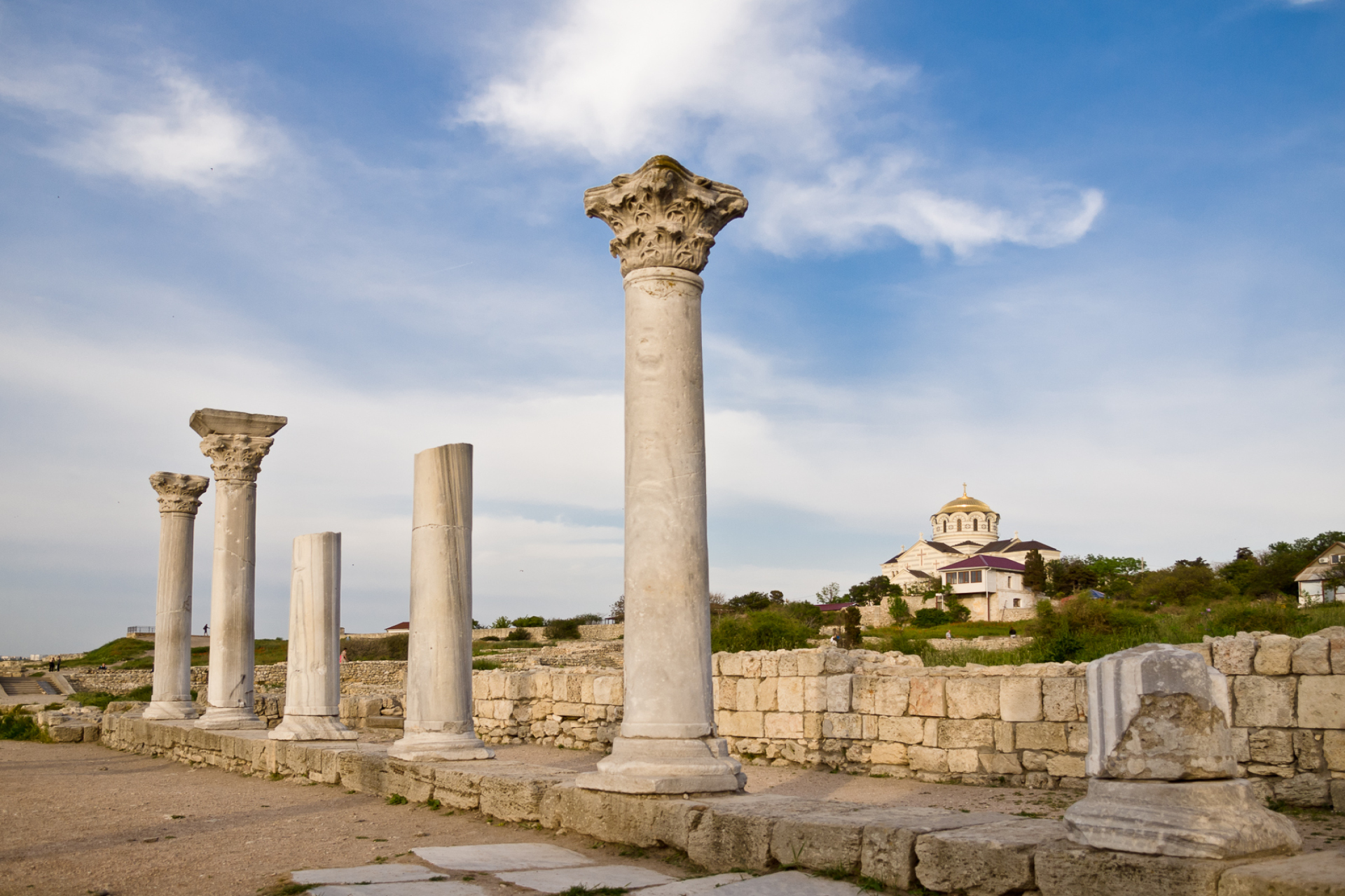 Ruins of an ancient Greek city, columns of the Corinthian order in front and a byzantine church on the background