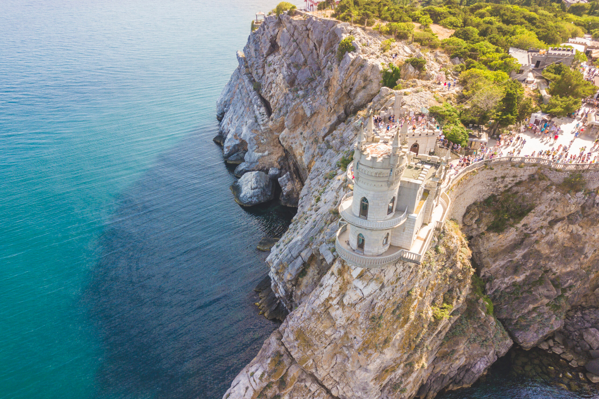 An aerial view of a beautiful castle on the top of a cliff and of the sea