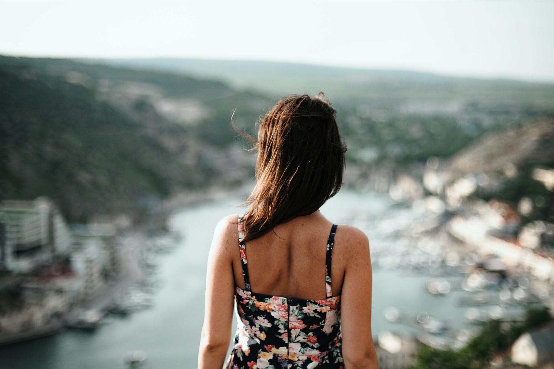 A back of a lady wearing a dress in front of the sea and mountains
