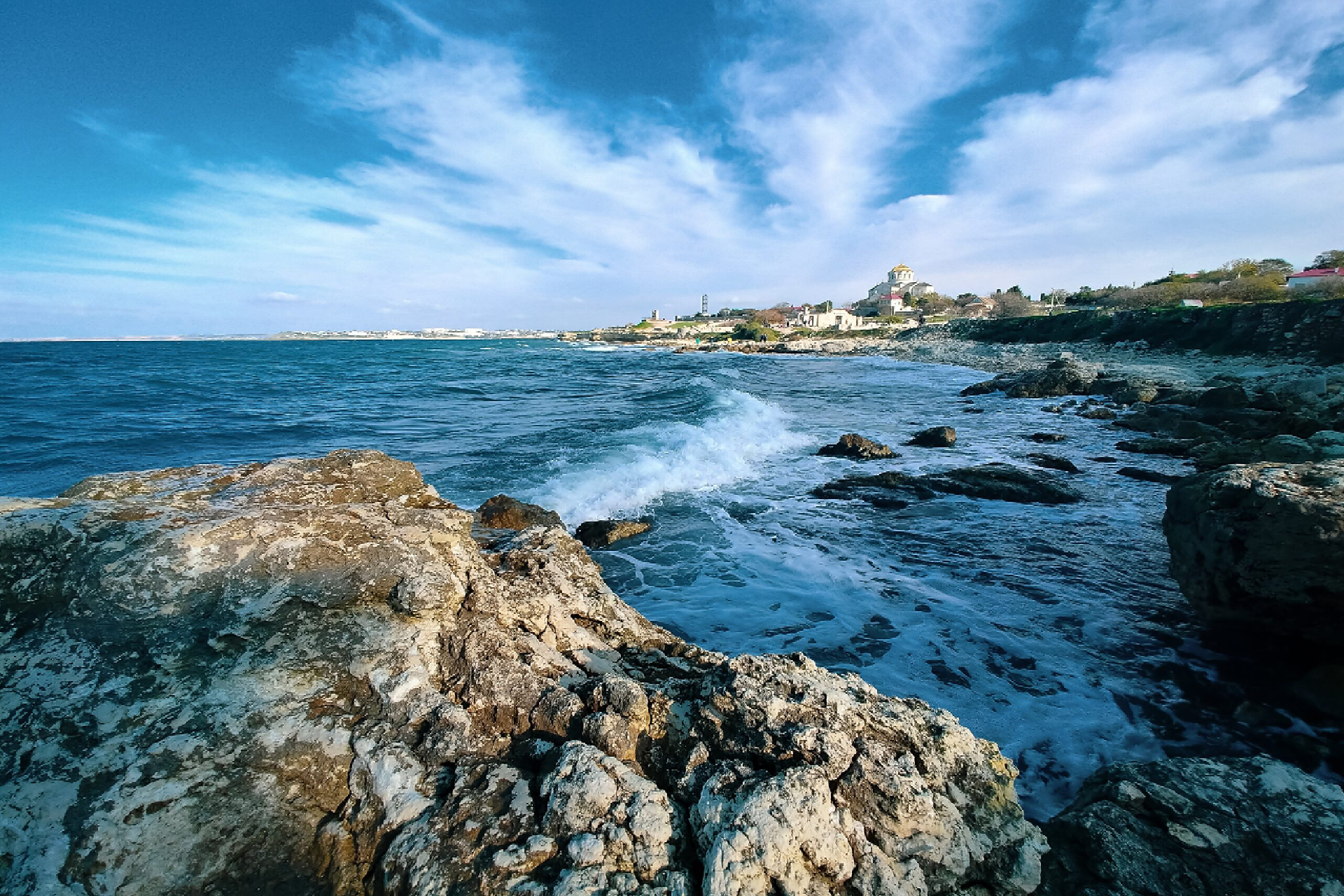 Rocky shore of the sea, ancient city in the background
