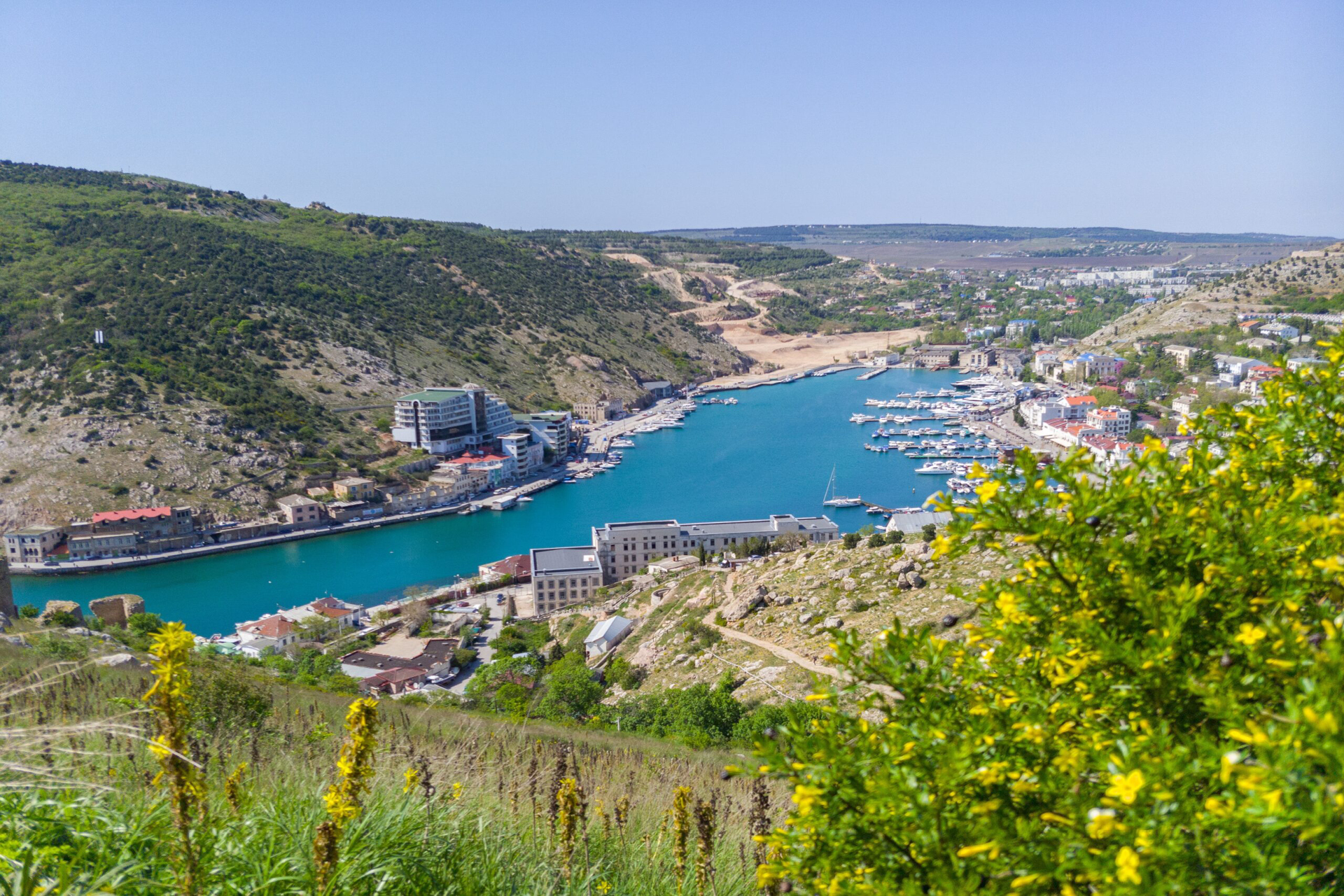The view from the hill of a city on the shores of a bay, sea water of a beautiful blue color