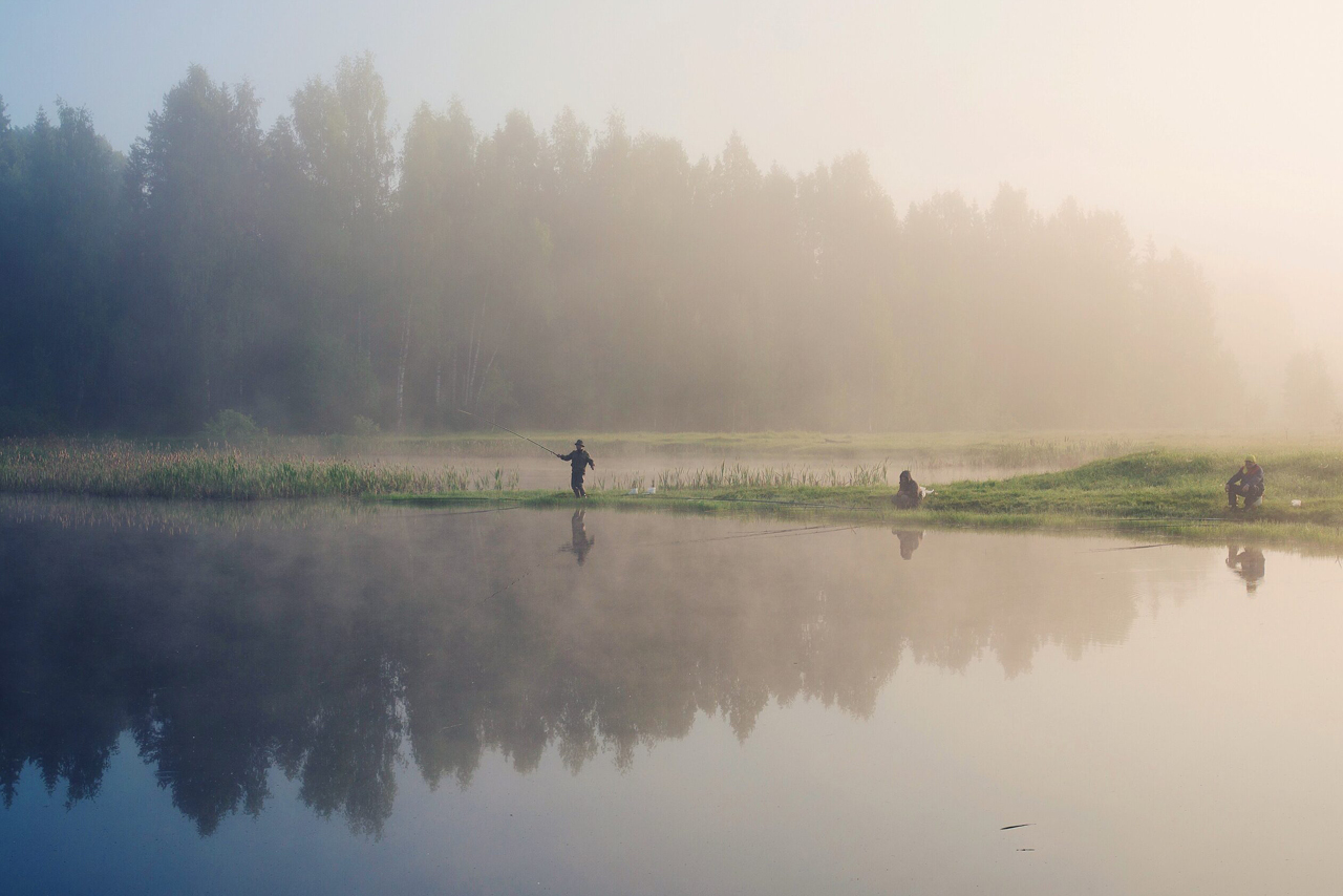 Fishers on the lake, fog in the early morning on the lake and a forest behind