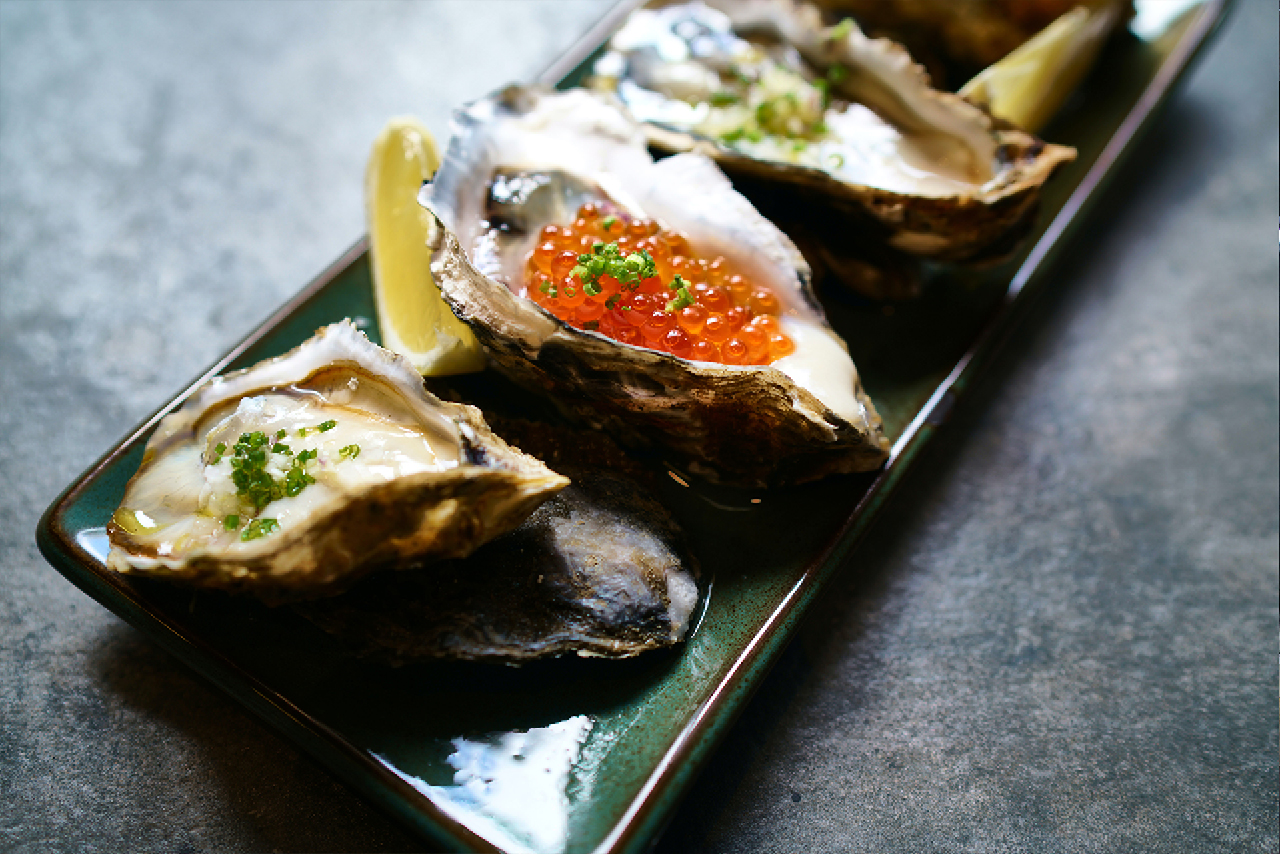 A plate with oysters served with red caviar and other fillings
