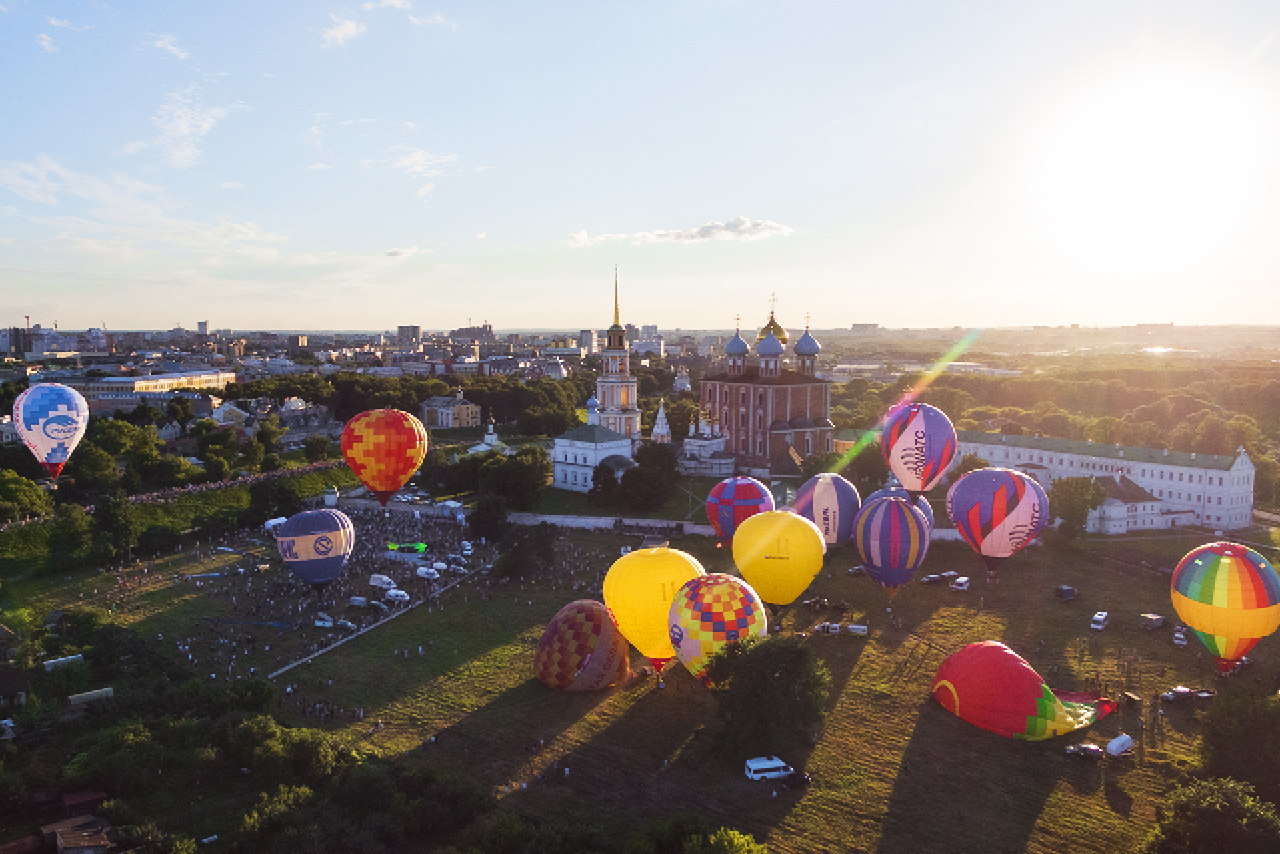 Colorful hot air balloons fly over orthodox red and white cathedral with blue and gilded domes, bell tower and green gardens around, buildings of soviet times on the background