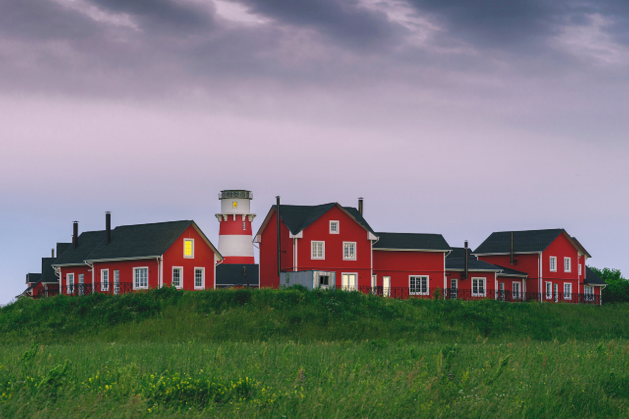 A small village in Russia in Norwegian style with a lighthouse, cozy red houses in a green field , grey sky