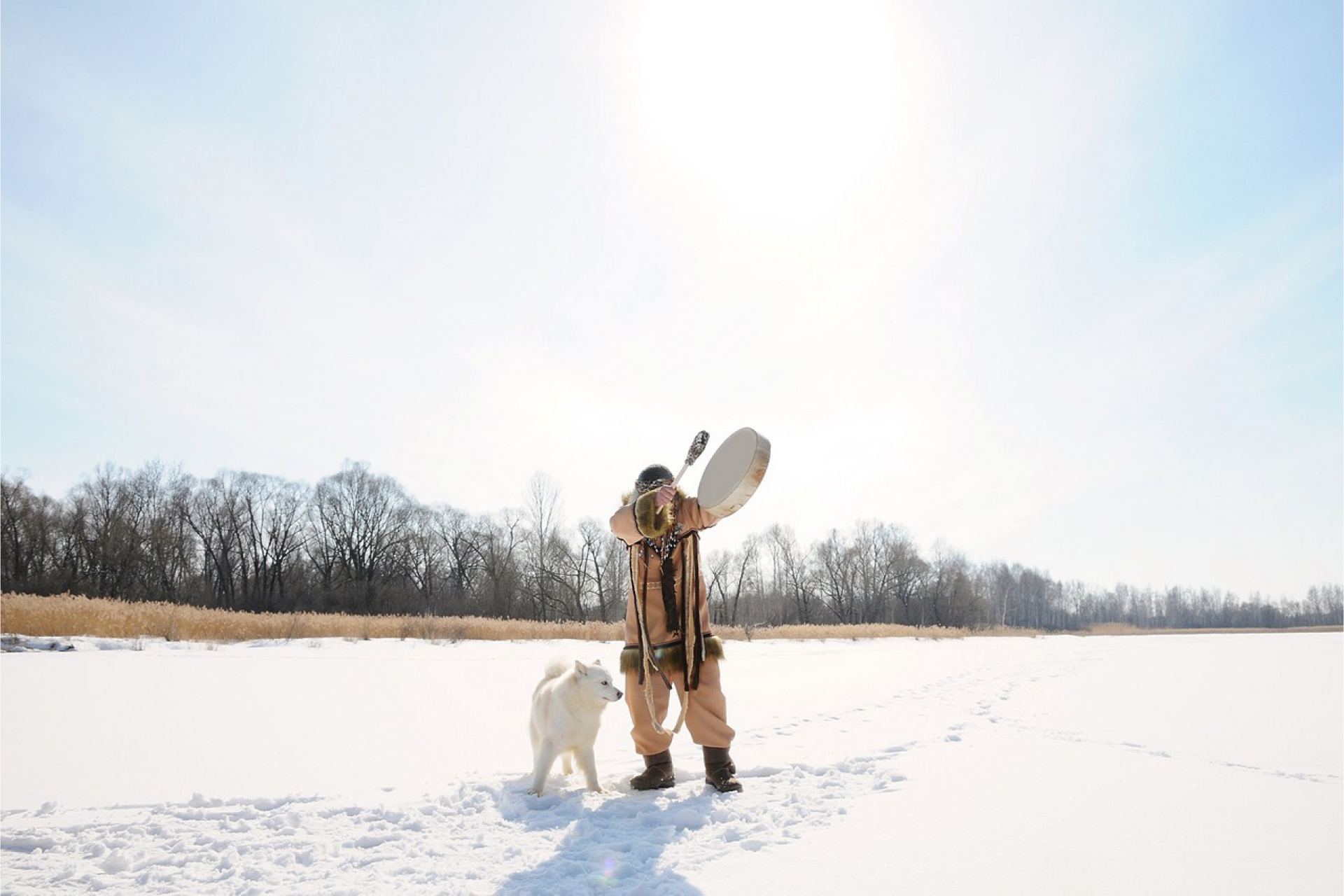A Shaman with a tambour and his dog in a winter landscape
