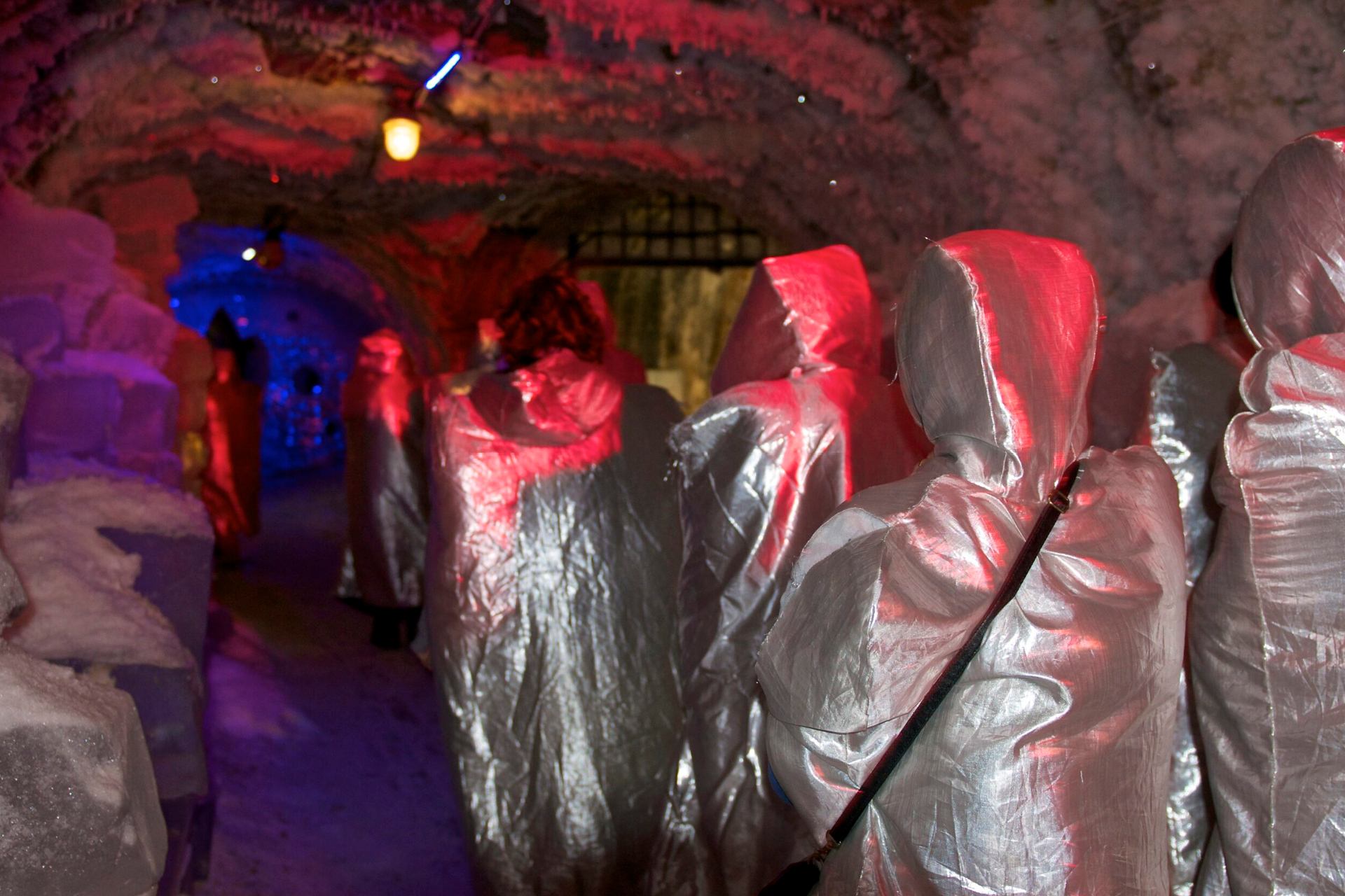 A group of people wearing silver cold protective coats inside of a natural iced cave