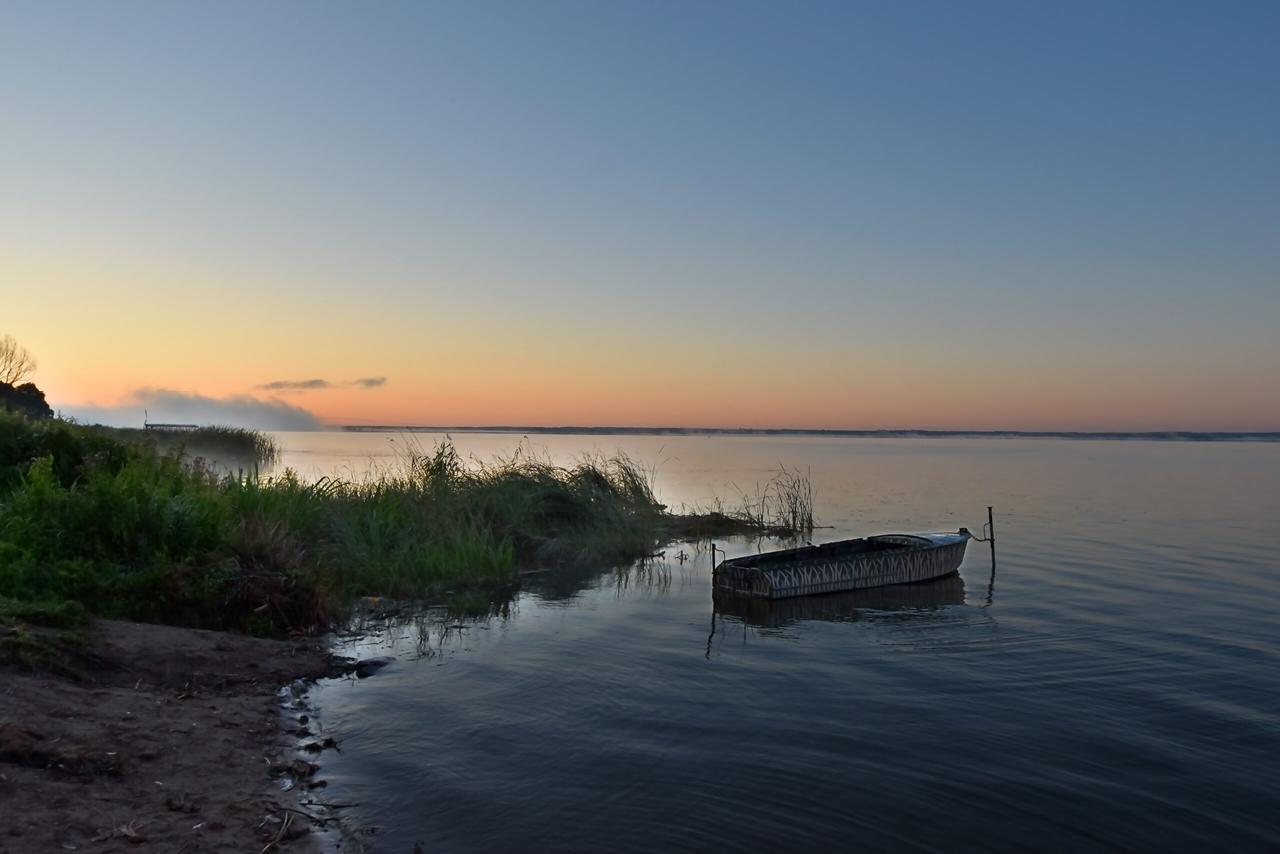 A small wooden boat attached in the lake, calm landscape scene, Central Russia