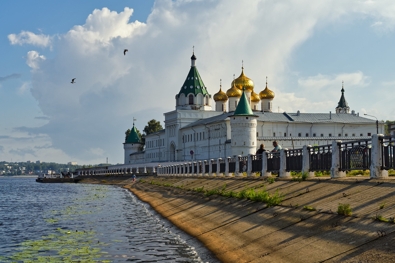 A monastery on the embankment of a river. Architectural ensemble of Orthodox churches surrounded with white wall, tower with green roof and church gilded onion domes