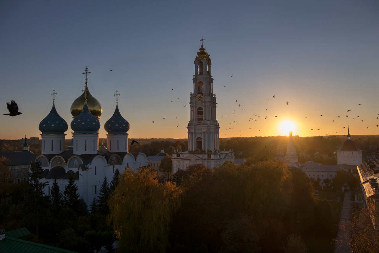 Aerial view of a monastery. Tall bell tower with an orthodox cross on the top, the upper part of a church with a gilded dome in the center and blue smaller domes with golden stars around. Orthodox monastery during the sunset.