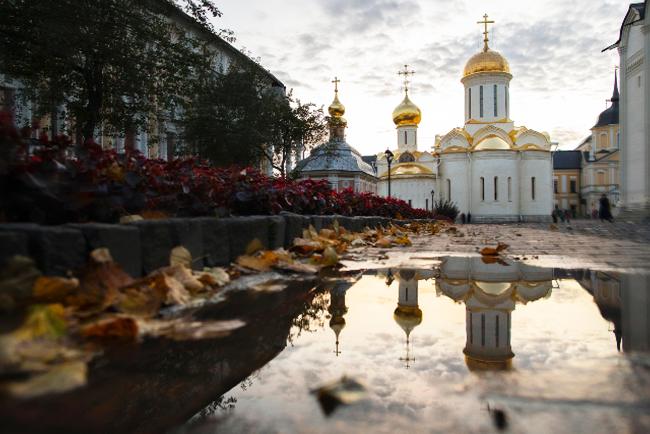 The territory of a monastery, small white churches with gilded domes reflected in the puddle of water, stone-block pavement with yellow leaves in autumn