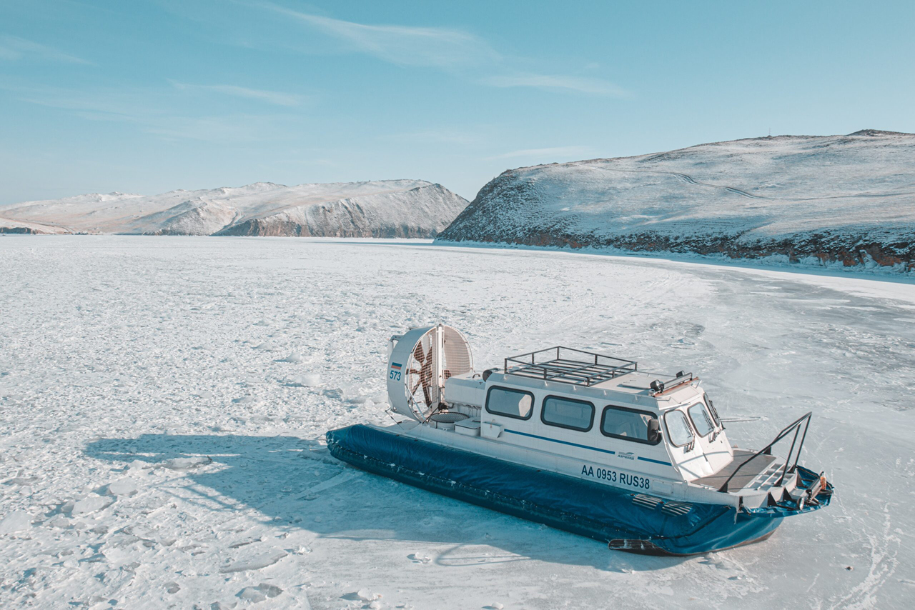 A Hovercraft on the ice of lake Baikal in winter, snowed up hills on the background