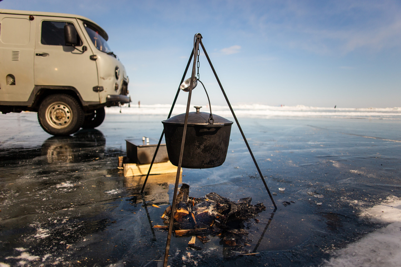 A cooking pot on open fire, a bonfire on the iced surface, a Russian off-road minibus