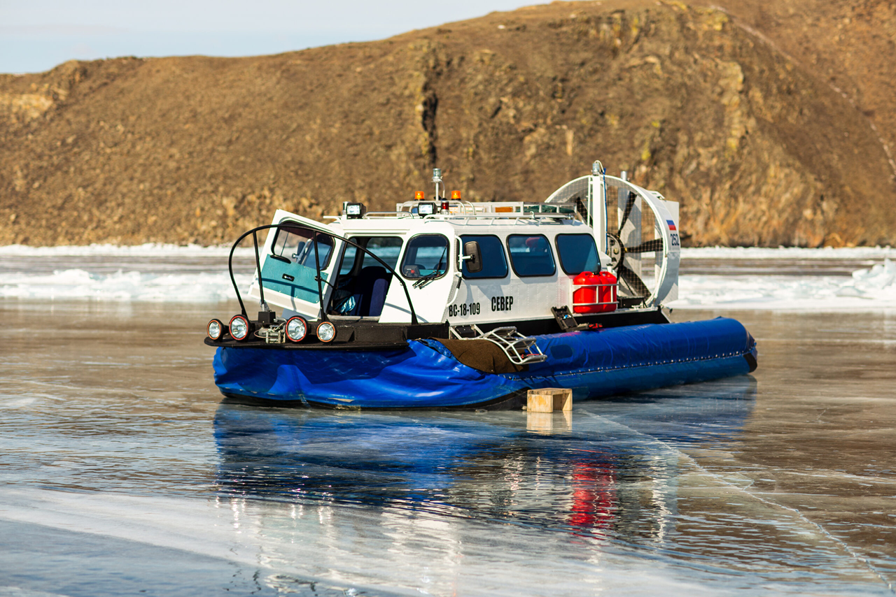 A Hovercraft on the ice of lake Baikal in winter, hills on the background