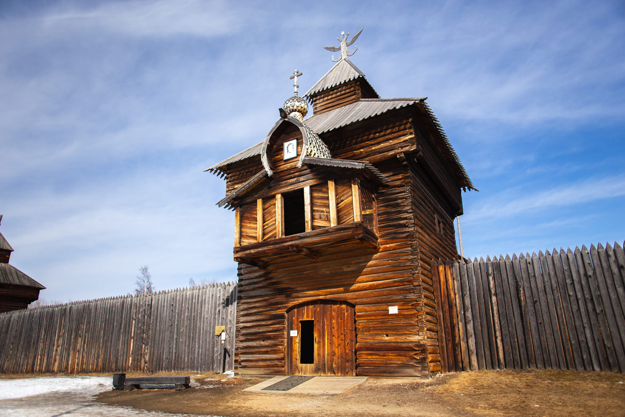 A wooden church and wooden fence around it