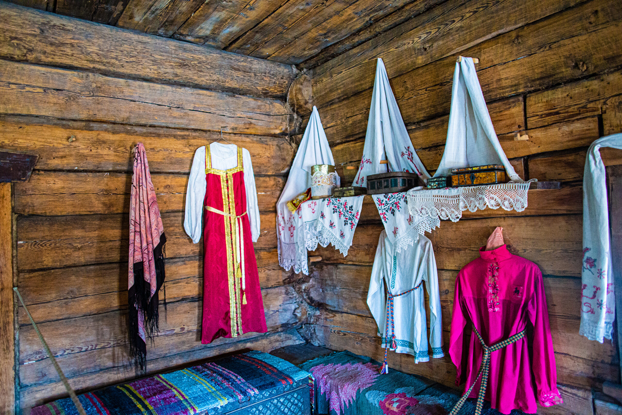 Interior of an old Russian wooden house, traditional Russian clothes hanged on the wall, boxes on a shelf decorated with white tissues